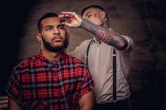 Il parrucchiere tatuato professionista antiquato fa un taglio di capelli ad un cliente afroamericano su buio strutturato immagini stock libere da diritti