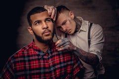 Il parrucchiere tatuato professionista antiquato fa un taglio di capelli ad un cliente afroamericano su buio strutturato fotografia stock