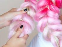 Il parrucchiere tesse le trecce con la bella bionda dei kanekalons rosa fotografia stock libera da diritti
