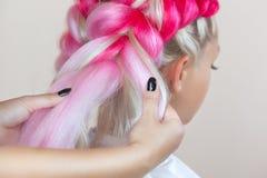 Il parrucchiere tesse le trecce con la bella bionda dei kanekalons rosa fotografie stock libere da diritti