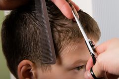 Il parrucchiere tiene un pettine e le forbici in sua mano e fa un ragazzo della pettinatura fotografia stock