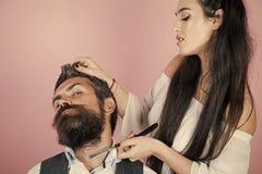 Il parrucchiere tosa il cliente nel parrucchiere Negozio di barbiere di visita del cliente dei pantaloni a vita bassa fotografie stock libere da diritti