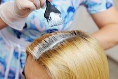 Il parrucchiere usa una spazzola per applicarsi la tintura ai capelli, per la d Fotografia Stock
