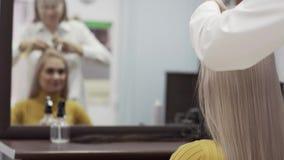 Il parrucchiere vago Woman Reflected In lo specchio fa la pettinatura stock footage