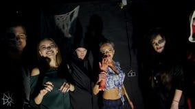 Il partito di Halloween, la notte, penombra, nei raggi di luce, giovani spaventa gli spettatori, ognuno è vestito dentro stock footage
