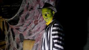 Il partito di Halloween, la notte, penombra, nei raggi di luce, un uomo con un trucco terribile, con un fronte verde e un cappell video d archivio