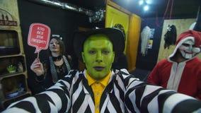 Il partito di Halloween, la notte, ritratto di un uomo con un fronte verde, portante un cappello, con un trucco terribile, gracch stock footage