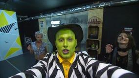 Il partito di Halloween, la notte, ritratto di un uomo con un fronte verde, portante un cappello, con un trucco terribile, gracch archivi video