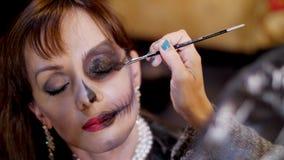 Il partito di Halloween, il primo piano, truccatore disegna un trucco terribile sul fronte di una donna castana per un partito di archivi video