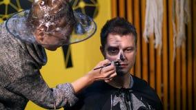 Il partito di Halloween, truccatore disegna un trucco terribile sul fronte di un uomo per un partito di Halloween Nei precedenti video d archivio