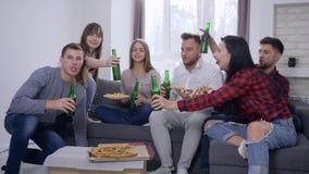 Il partito domestico, amici della gioventù della società mangia la pizza e la birra della bevanda mentre guarda la seduta della t video d archivio