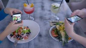 Il partito fresco, amici femminili usa le tecnologie mobili moderne ed immagini di presa di bello alimento per i media sociali du archivi video
