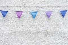 Il partito variopinto inbandiera la stamina che appende sul fondo bianco della parete Progettazione minima di stile dei pantaloni Fotografia Stock