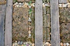 Il passaggio pedonale ha fatto il vecchi legno e pietra sull'erba Immagine Stock
