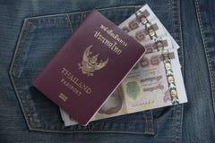 Il passaporto della Tailandia ed i soldi tailandesi in jeans intascano Immagine Stock Libera da Diritti