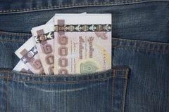 Il passaporto della Tailandia ed i soldi tailandesi in jeans intascano Immagine Stock