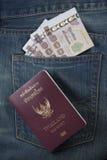 Il passaporto della Tailandia ed i soldi tailandesi in jeans intascano Fotografie Stock