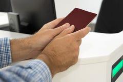 Il passaporto di attesa dell'uomo controlla l'aeroporto Immagine Stock