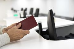Il passaporto di attesa della donna più anziana controlla l'aeroporto Immagine Stock