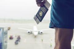 Il passeggero con il passaporto e un biglietto di aeroplano nel terminale di aeroporto attende la partenza fotografia stock