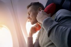Il passeggero maschio dell'aeroplano ascolta musica e gode del cuscino per il sonno nella sedia fotografia stock libera da diritti