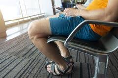 Il passeggero nel salotto dell'aeroporto si siede nel sedile con un passaporto e un biglietto a disposizione Concetto di viaggio fotografia stock