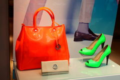 Handbag and shoe store. Orange bag and green shoes at Il Passo shop located in a mall.A store selling expensive handbags and shoes and other woman accessories Stock Photo