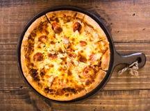 Il pasto della pizza di merguez è servito in pentola sulla tavola di legno Fotografia Stock