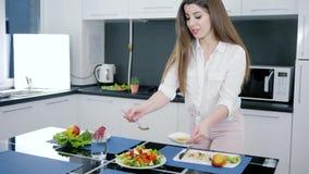 Il pasto sano, ragazza versa l'olio d'oliva su insalata fresca con i verdi ed i pomodori al rallentatore archivi video