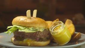 Il pasto succoso dell'hamburger del manzo su un panino dei semi di sesamo ha completato con bacon e formaggio ed è servito con le archivi video