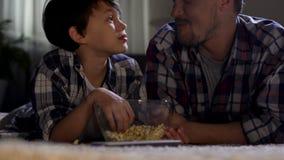 Il patrigno ed il figlio che guardano la TV a casa fino a tardi e mangiano gli alimenti industriali, la prossimità stock footage