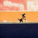 il pattinatore che salta davanti alla parete arancio Fotografie Stock