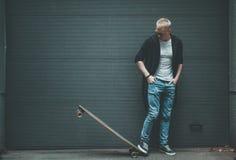 Il pattinatore del giovane sta stando con il bordo lungo Fotografia Stock Libera da Diritti