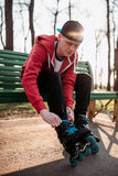 Il pattinatore del rullo che si siede sul banco e allaccia i pattini Immagine Stock Libera da Diritti