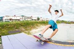 Il pattinatore dell'adolescente in un cappuccio e gli shorts sulle rotaie su un pattino in un pattino parcheggiano Immagini Stock Libere da Diritti