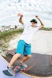Il pattinatore teenager appende su sopra una rampa su un pattino in un parco del pattino Immagine Stock Libera da Diritti