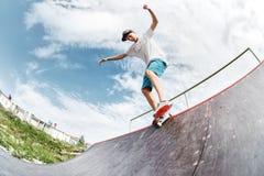 Il pattinatore teenager appende su sopra una rampa su un pattino in un parco del pattino Fotografie Stock