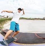 Il pattinatore teenager appende su sopra una rampa su un pattino in un parco del pattino Immagini Stock