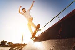 Il pattinatore teenager appende su sopra una rampa su un pattino in un parco del pattino Fotografia Stock
