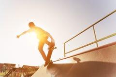 Il pattinatore teenager appende su sopra una rampa su un pattino in un parco del pattino Fotografia Stock Libera da Diritti
