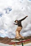 Il pattinatore teenager in maglietta felpata e jeans di maglia con cappuccio fa scorrere sopra un'inferriata su un pattino in un  Fotografie Stock