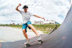 Il pattinatore teenager supera una rampa su un pattino in un parco del pattino Fotografie Stock