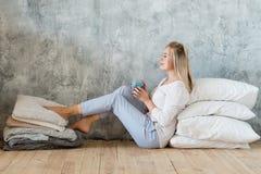 Il pavimento della donna appoggia lo svago domestico comodo del caffè immagine stock