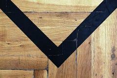 Il pavimento di legno consumato della palestra con la marcatura variopinta allinea Immagini Stock