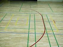 Il pavimento di legno della palestra con il campo da giuoco allinea, legno duro del parquet nella corte della scuola Immagine Stock