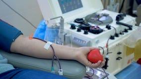 Il paziente dona il sangue tramite i tubi e le siringhe in un centro moderno della trasfusione stock footage