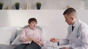Il paziente femminile invecchiato è menzogne orizzontale e parlare della suoi malattia e dolore archivi video
