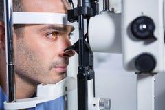 Il paziente maschio che ottiene la sua cornea ha controllato con la lampada a fessura fotografie stock libere da diritti