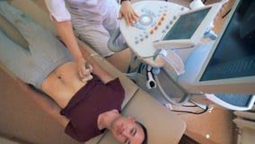 Il paziente maschio sta subendo la procedura di ultrasuono in una funzione medica archivi video
