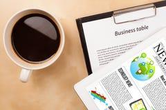 Il pc della compressa mostra le notizie sullo schermo con una tazza di caffè su uno scrittorio Immagini Stock Libere da Diritti